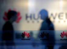 """Staff and visitors walk pass the lobby at the Huawei office in Wuhan, central China's Hubei province on October 8, 2012.  Beijing on October 8 urged Washington to """"set aside prejudices"""" after a draft Congressional report said Chinese telecom firms Huawei and ZTE were security threats that should be banned from business in the US.   CHINA OUT      AFP PHOTO        (Photo credit should read STR/AFP/GettyImages)"""